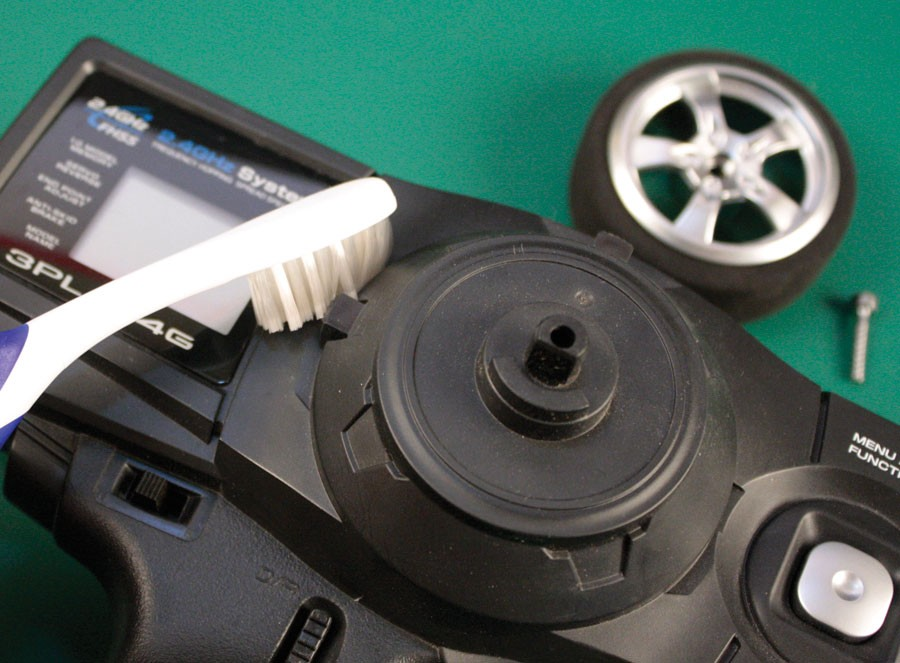 First, use the appropriate driver to remove the screw at the center of the steering wheel and take the wheel off. It is critical to remove all dust, dirt and residue from the transmitter's case. Paint needs a clean surface for best adhesion. An old toothbrush works well for getting into the seams.