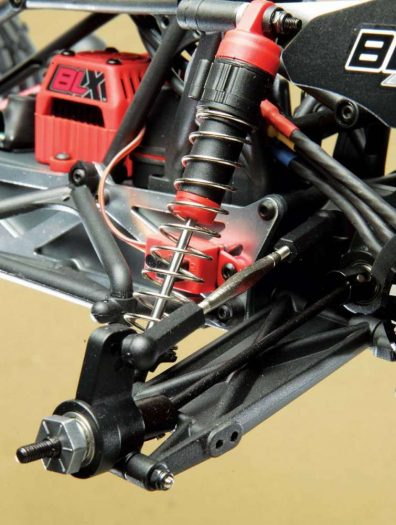 In the rear we can see the new metal hexes and the stiffer solid suspension arm. The shocks also get dressed up with red plastic caps to match the electronics.