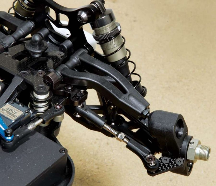 Carbon fiber steering arms on the knuckle help keep weight down. The sweep on the upper pivot ball arm allows for plenty of clearance when the steer- ing rack swings under it.