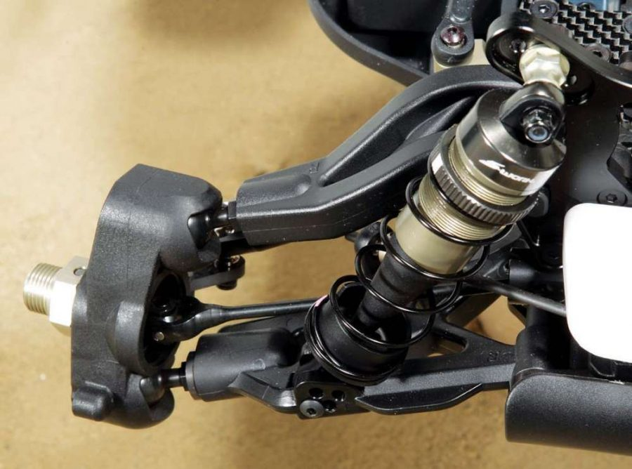Here you can see the hard coated pivot balls and the very thin driveshafts for reduced rotating mass. The suspension arm also has plenty of tuning options for the lower shock mount location and we like the tall shock perch that reduces the chance of losing the cup in a crash.
